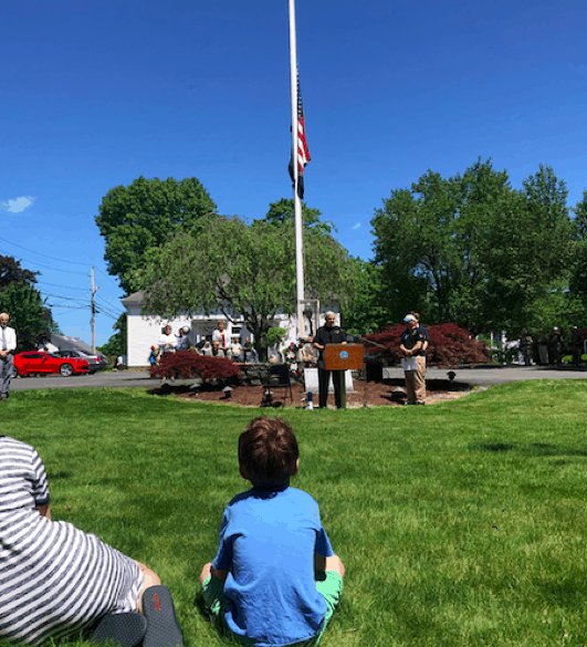 Pic of a kid sitting and watching a Veteran speak after a Memorial Day march.